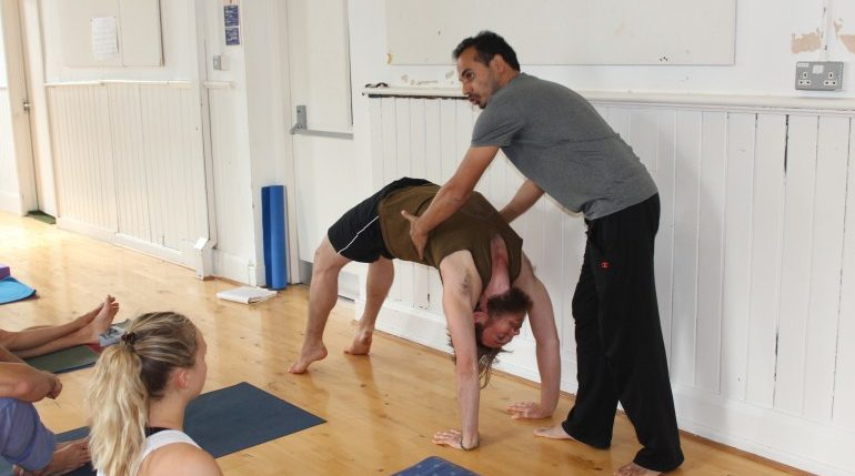 Teacher showing Yoga students Urdvha Danurasana