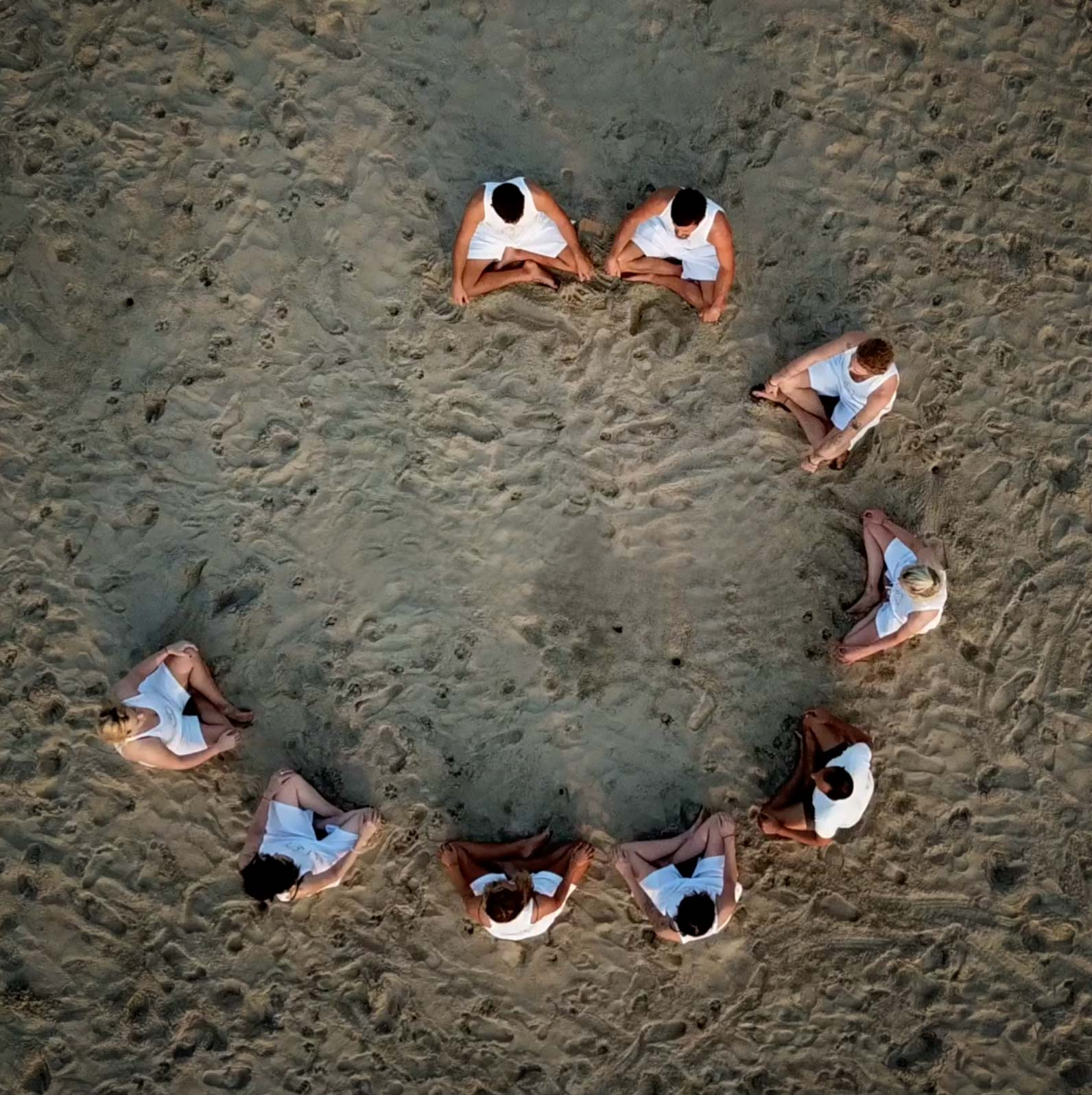 Arial shot of yoga students in meditation on beach
