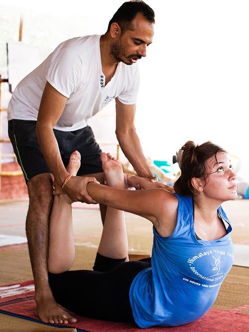 Yoga teacher stretching a student