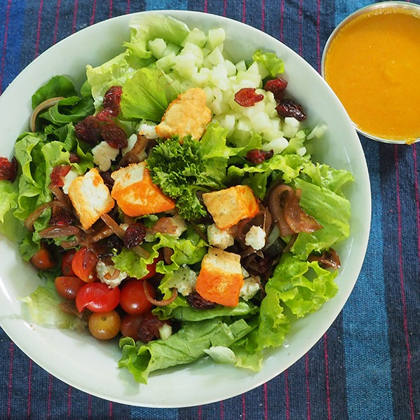 Salad and yellow sauce in bowl