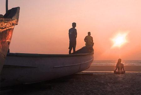 Girl meditating on beach at sunset